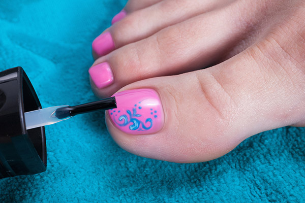 applying pink and blue nail paint