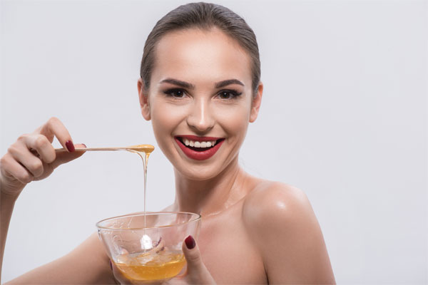 girl with bowl of honey in nail studio
