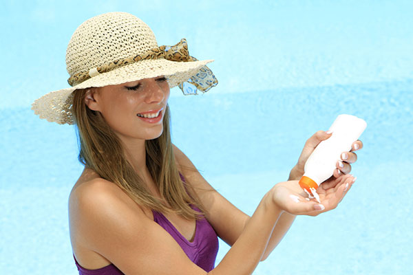 women wearing hat and applying sunscreen